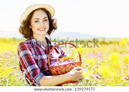 Portrait of young woman holding basket with flowers outside - stock photo