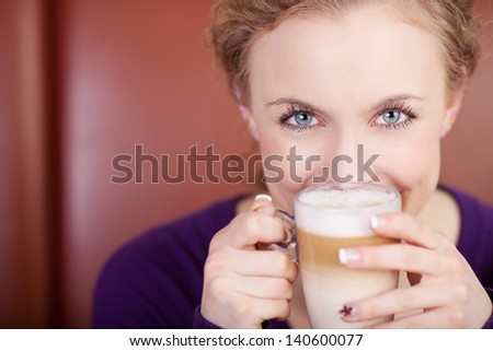 Portrait of young woman holding cafe latte cup in coffee shop - stock photo