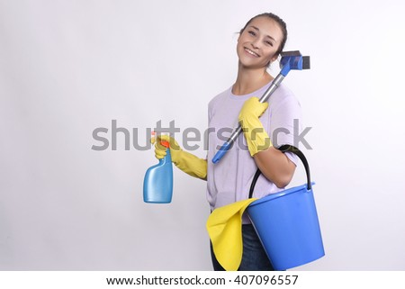 Portrait of young woman holding cleaning products. Isolated on white background. - stock photo