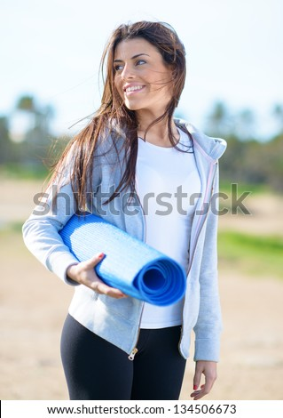 Portrait Of Young Woman Holding Exercise Mat; Outdoors - stock photo