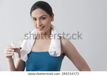 Portrait of young woman holding glass of water against gray background - stock photo