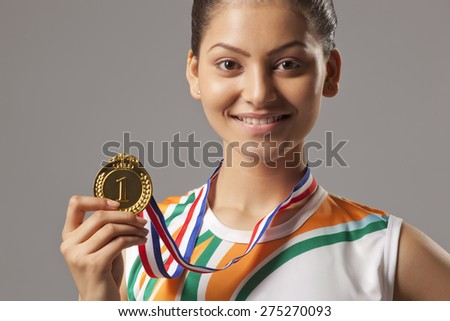 Portrait of young woman holding gold medal isolated over gray background - stock photo
