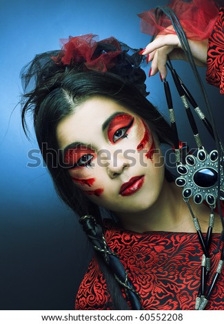 Portrait of young woman in black and red silk  with creative make-up - stock photo