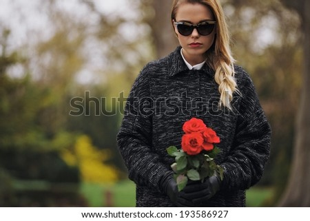 Portrait of young woman in black dress at graveyard holding fresh flowers. Caucasian female at cemetery with red roses. - stock photo