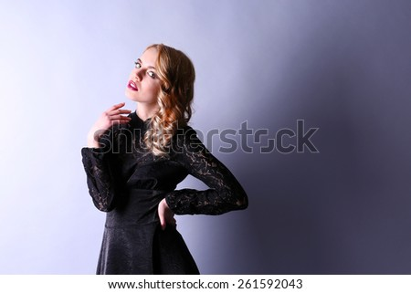 Portrait of young woman in black dress on light background - stock photo