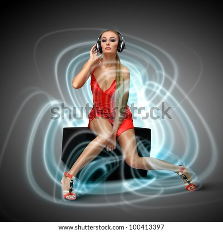 Portrait of young woman in evening dress with headphones - stock photo