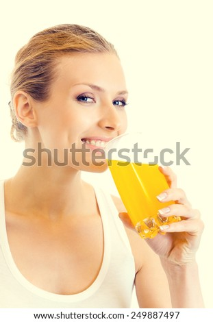 Portrait of young woman in fitness wear drinking orange juice - stock photo
