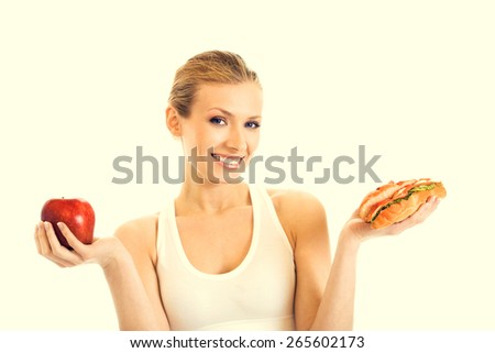 Portrait of young woman in fitness wear with sandwich and red apple, beauty and healthy eating concept - stock photo