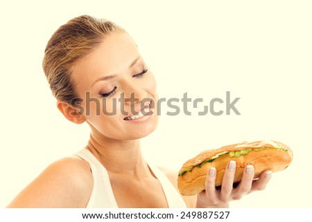 Portrait of young woman in fitness wear with sandwich, beauty and healthy eating concept. - stock photo