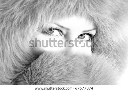 Portrait of young woman in furry hat. High key, black and white image - stock photo