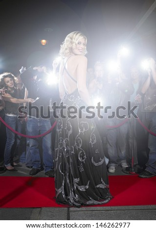 Portrait of young woman in gown posing for paparazzi on the red carpet - stock photo