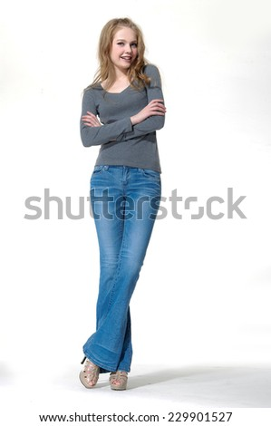Portrait of young woman in jeans standing full-length - stock photo