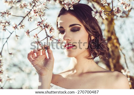Portrait of young woman in the flowered garden in the spring time. Almond flowers blossoms. Girl dressed in white like a bride. - stock photo