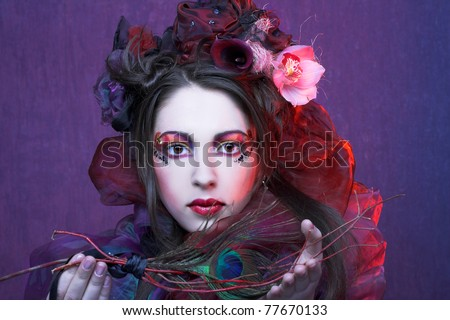 Portrait of young woman in violet showl and with exotic flowers in her hair. - stock photo