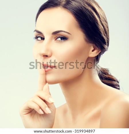 Portrait of young woman keeping finger on her lips and asking to keep quiet - stock photo