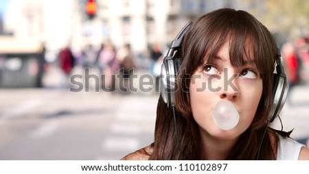portrait of young woman listening to music with bubble gum against a crowded city - stock photo