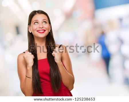 Portrait Of Young Woman Looking Up and Gesturing, indoor - stock photo
