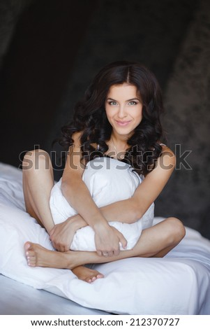 Portrait of young woman lying at the bed at early morning. Beautiful young woman with attractive smile sitting embracing pillow - indoors. Portrait of a pretty woman relaxing in bed. - stock photo