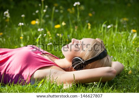 Portrait Of Young Woman Lying On Grass And Listening To Music With Headphones - stock photo