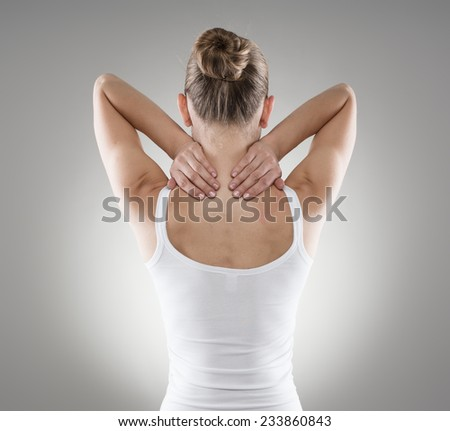 Portrait of young woman massaging her painful neck over grey background. Muscle spasm and backache concept.  - stock photo