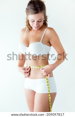 Portrait of young woman measuring her waist by measure tape. - stock photo