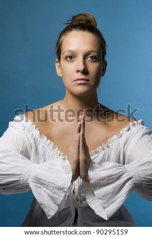 Portrait of young woman meditating in  isolation - stock photo