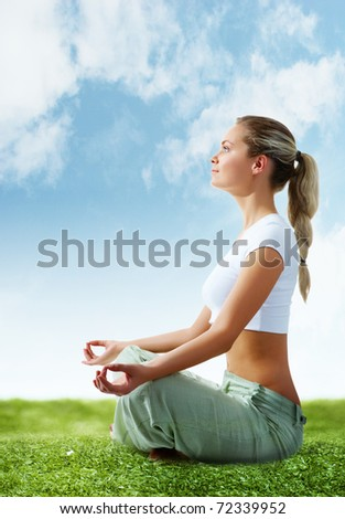 Portrait of young woman meditating in pose of lotus on green grass - stock photo