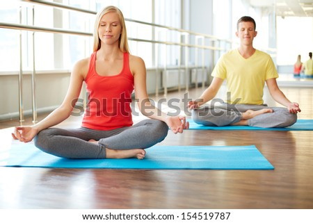 Portrait of young woman meditating in pose of lotus with guy on background - stock photo