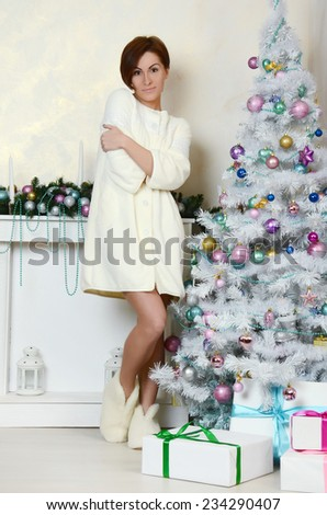 Portrait of  young woman near Christmas tree - stock photo