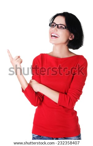 Portrait of young woman pointing up. - stock photo