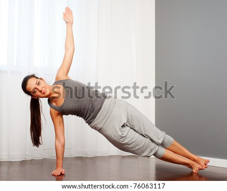 portrait of young woman practicing yoga in room - stock photo