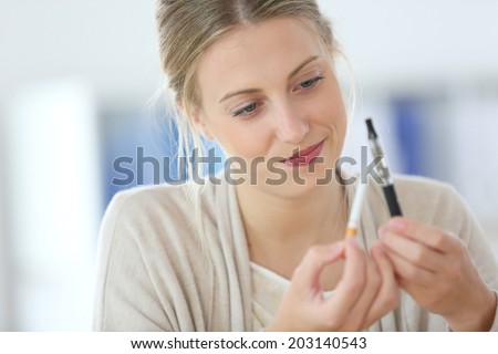 Portrait of young woman ready to opt for e-cigarette - stock photo