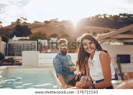 Portrait of young woman sitting by pool with friends having a party in evening. She is smiling and looking away. Young people enjoying a rooftop party at sunset. - stock photo
