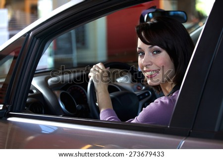 Portrait of young woman sitting in driver's seat at car dealership - stock photo