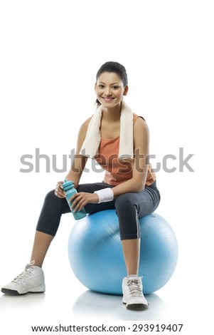 Portrait of young woman sitting on a fitness ball after workout over white background - stock photo