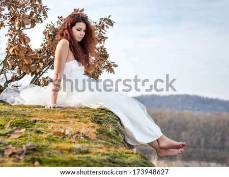 portrait of young woman sitting on green and yellow moss on the edge of a cliff - stock photo