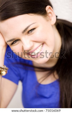 Portrait of young woman sitting outdoors and smiling - stock photo
