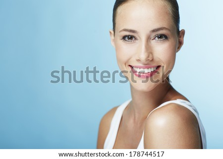 Portrait of young woman smiling against blue background - stock photo
