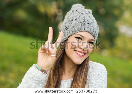 Portrait of young woman smiling in a park with victory sign. - stock photo