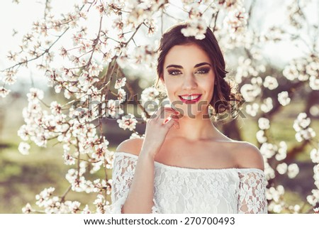 Portrait of young woman smiling in the flowered garden in the spring time. Almond flowers blossoms. Girl dressed in white like a bride. - stock photo