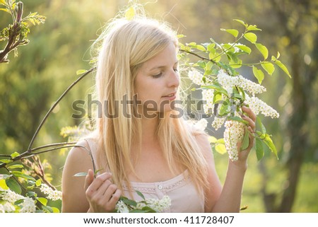 Portrait of young woman smiling in the flowered garden in the spring time.. Girl dressed in white like a bride. - stock photo