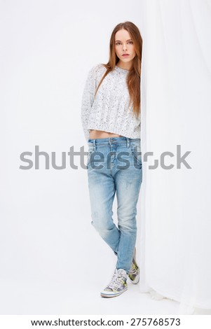 Portrait of young woman standing against white curtains. - stock photo