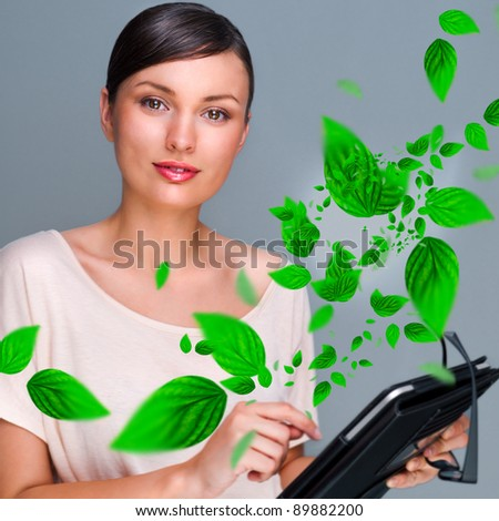 Portrait of young woman standing indoors at her office and working. Green leaves are floating around him. Business using Green power concept. - stock photo