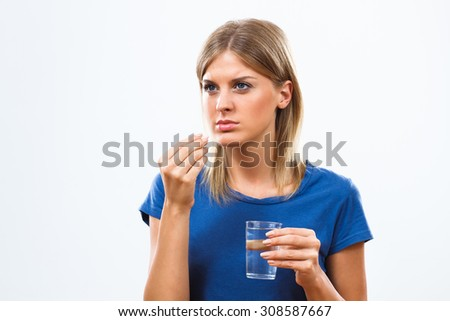 Portrait of young woman taking pills.Woman taking pills - stock photo
