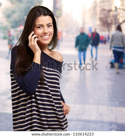 portrait of young woman talking on mobile at street - stock photo