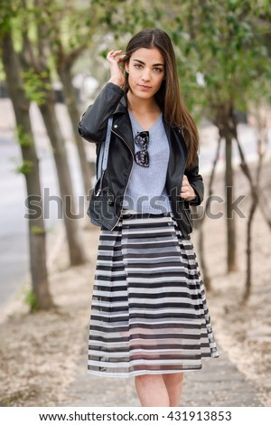 Portrait of young woman touching her hair with her hand in urban background wearing casual clothes. Girl wearing striped skirt, sweater and leather jacket - stock photo