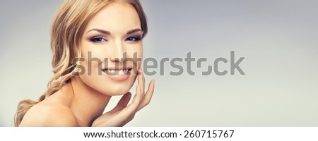 Portrait of young woman touching skin or applying cream, with blank copyspace area for text or slogan. Beauty and health concept. - stock photo