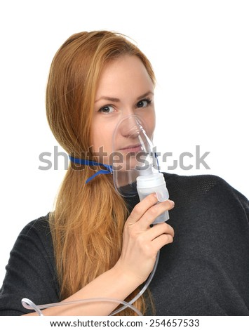 Portrait of young woman using nebulizer for respiratory inhaler Asthma Treatment isolated on a white background - stock photo