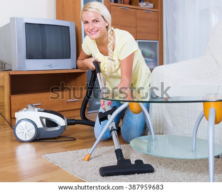 portrait of young woman using vacuum cleaner during regular clean-up - stock photo