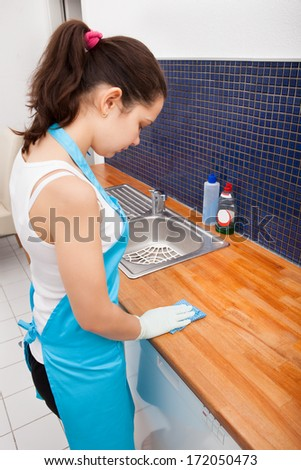 Portrait Of Young Woman Wearing Apron Cleaning Kitchen Worktop - stock photo